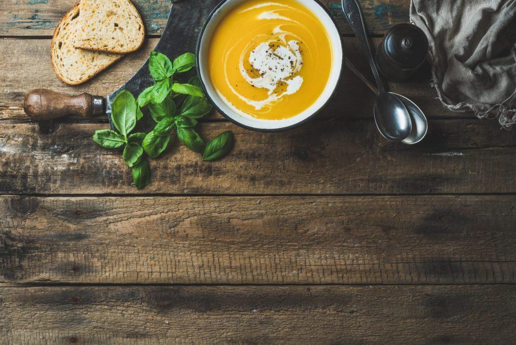 一碗南瓜奶油湯配新鮮羅勒香料和烤麵包片